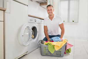 Man Putting Colorful Towels Into The Washing Machineの写真素材 [FYI00778432]