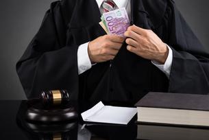 Judge Hiding Banknote At Deskの写真素材 [FYI00778433]