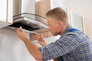 Repairman Repairing Kitchen Extractor Filterの写真素材 [FYI00778435]