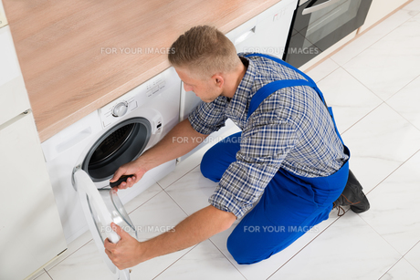 Worker In Overall Fixing Washerの写真素材 [FYI00778439]