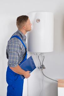 Repairman Looking At Dial Gauge On Electric Boilerの写真素材 [FYI00778446]