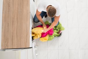 Man Putting Clothes In Washing Machineの写真素材 [FYI00778452]