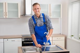 Repairman Installing Faucet Of Kitchen Sinkの写真素材 [FYI00778466]
