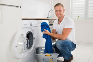 Man Loading Washing Machine With Clothesの写真素材 [FYI00778467]