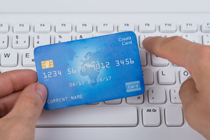 Hands Holding Credit Card On A Keyboardの写真素材 [FYI00778473]