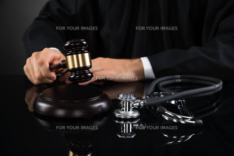 Close-up Of Judge Hitting Gavel With Stethoscopeの写真素材 [FYI00778482]