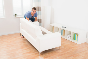 Young Man Moving Sofaの写真素材 [FYI00778493]