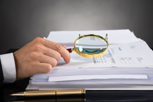 Businessperson Hands Analyzing Receipt With Magnifying Glassの写真素材 [FYI00778497]