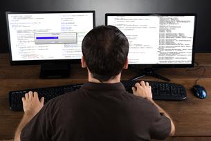 Man Programming Code On Computersの写真素材 [FYI00778498]