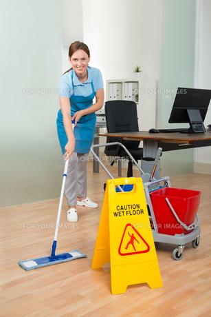 Female Janitor Cleaning Hardwood Floor In Officeの写真素材 [FYI00778537]