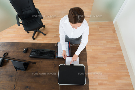 Young Businesswoman Using Printer In Officeの写真素材 [FYI00778575]