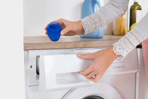 Female Hands Pouring Detergent In The Washing Machineの写真素材 [FYI00778578]