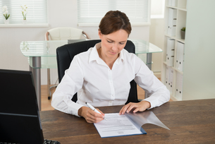 Businesswoman Reading Document At Deskの写真素材 [FYI00778582]