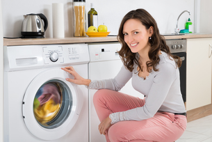 Woman Cleaning Clothes In Washing Machineの写真素材 [FYI00778602]