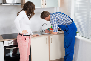Woman Looking At Plumber Fixing Sinkの写真素材 [FYI00778604]