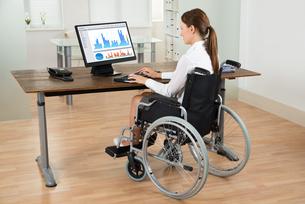 Businesswoman On Wheelchair Analyzing Graphの写真素材 [FYI00778609]