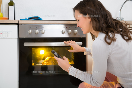 Woman With Mobile Phone While Cooking Chickenの写真素材 [FYI00778621]