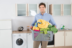 Man Carrying Basket With Heap Of Clothesの写真素材 [FYI00778632]