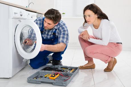 Repairman Repairing Washer In Front Of Womanの写真素材 [FYI00778645]