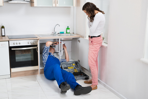 Repairman Repairing Pipe While Woman In The Kitchenの写真素材 [FYI00778646]