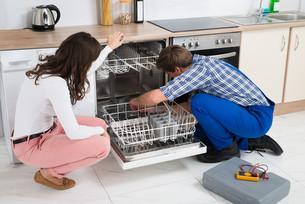 Woman Looking At Repairman Repairing Dishwasherの写真素材 [FYI00778648]