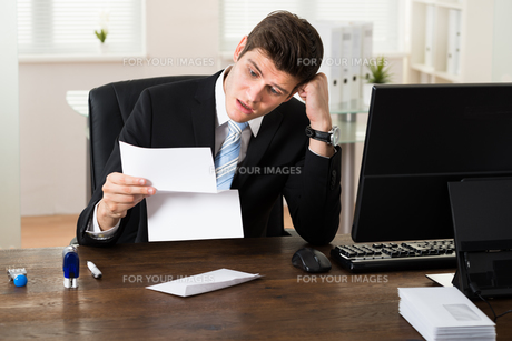 Shocked Businessman With Document In Officeの写真素材 [FYI00778724]