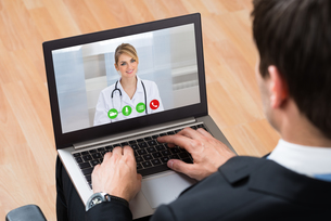 Businessperson Videochatting Online With Doctor On Laptopの写真素材 [FYI00778730]