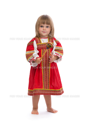 Little girl in red traditional dress with a wooden spoonの写真素材 [FYI00778857]