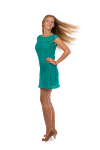 Beautiful girl in a turquoise dress with developing hair in the studio.の写真素材 [FYI00778866]