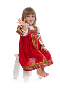 Little girl in red traditional dress on a chairの写真素材 [FYI00778879]