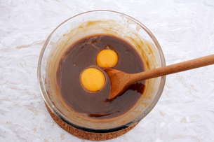 Stirring egg yolks into pecan pie fillingの写真素材 [FYI00779142]