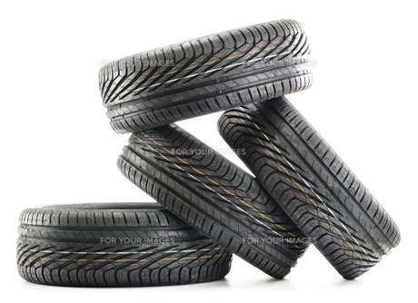 Four new black tires isolated on whiteの写真素材 [FYI00779180]