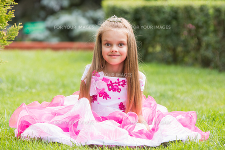 Girl princess sat on the lawn in the green gardenの写真素材 [FYI00779215]