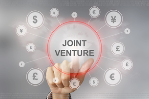 business hand pushing joint venture buttonの写真素材 [FYI00779225]