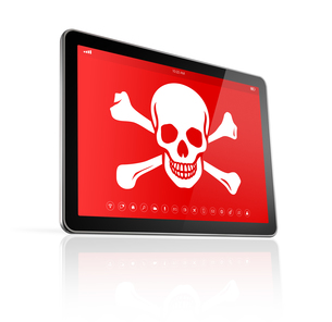 digital tablet PC with a pirate symbol on screen. Hacking conceptの素材 [FYI00780255]