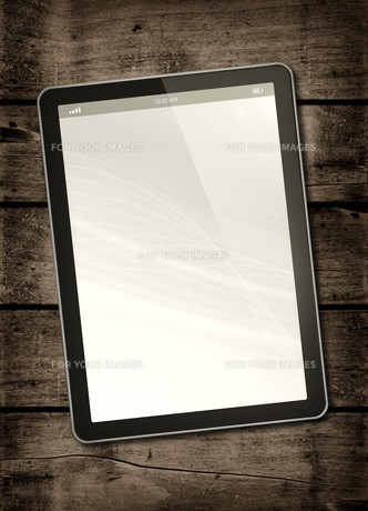 Digital tablet PC on a dark wood tableの写真素材 [FYI00780281]