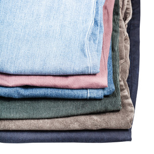 stack of different jeans and corduroys close upの写真素材 [FYI00780309]