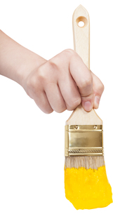 front view of painter hand with yellow paintbrushの素材 [FYI00780328]