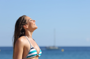 Woman breathing in summer vacations on the beachの写真素材 [FYI00780714]