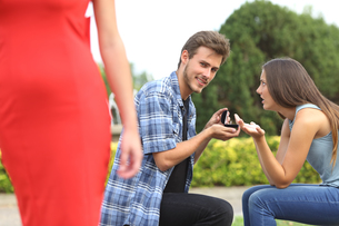 Unfaithful man looking another girl during proposalの写真素材 [FYI00780749]