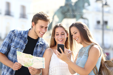 Three tourist friends consulting gps on smart phoneの写真素材 [FYI00780829]