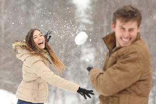 Couple playing with snow and girlfriend throwing a ballの写真素材 [FYI00780875]