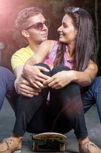 Young couple in love sitting on a skateboard outdoorsの写真素材 [FYI00780966]