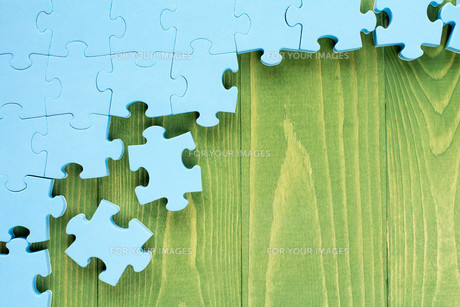 Puzzle on green wooden backgroundの素材 [FYI00780978]
