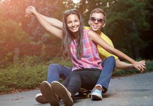 Young couple in love sitting on a skateboard outdoorsの写真素材 [FYI00780986]