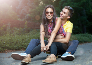 Young couple in love sitting on a skateboard outdoorsの写真素材 [FYI00780990]