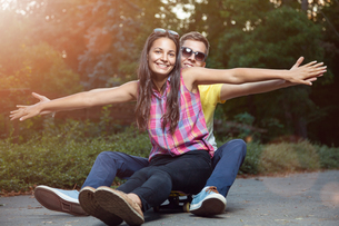 Young couple in love sitting on a skateboard outdoorsの写真素材 [FYI00781012]