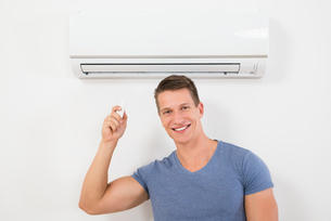 Man With Remote Control To Operate Air Conditionerの写真素材 [FYI00781054]