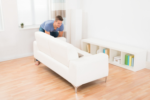 Young Man Moving Sofaの写真素材 [FYI00781059]