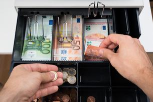 Person Hands With Money Over Cash Registerの写真素材 [FYI00781077]